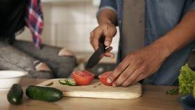 Langzame motie dichte omhooggaand van een jonge speelse scherpe tomaat van de mulatkerel voor salade, makend lunch met zijn meisj stock video