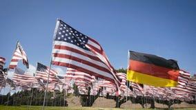 Langzame motie die Duitse vlag binnen - tussen Amerikaanse vlaggen golven diplomatiek concept stock videobeelden