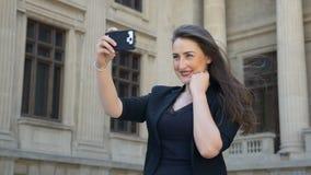 Langzame motie die van aantrekkelijke vrouw video nemen selfie terwijl het golven van haar mooi bruin haar stock videobeelden