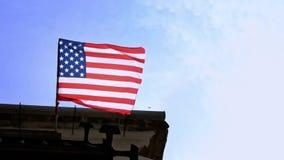 Langzame motie die van Amerikaanse vlag in de wind op vlaggestok bij de stad van Amerika golven stock videobeelden
