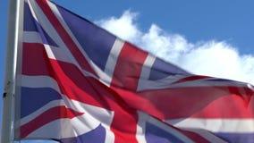 Langzame motie die van Engelse vlag in wind op vlaggestok bij een stad golven engeland stock footage