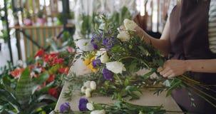 Langzame motie die van verkoopvrouw bloemen in bloemenwinkel schikken die tot samenstelling leiden stock videobeelden