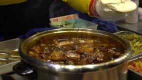 Langzame Motie die van verkoper gestoofd varkensvlees koken bij kant van de wegtribunes Heerlijk Vlees stock footage