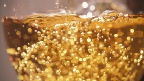 Langzame motie in een glas om een gele drank met bellen te gieten stock footage
