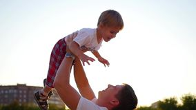 Langzame Motie een jonge vader die zijn lachende baby omhoog in de lucht werpen Openlucht recreatie stock footage