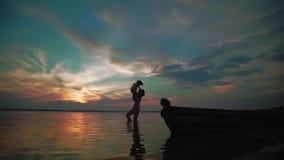 Langzame Motie Een vrouw heft haar baby van het meer en vreugdevol draaien rond met haar op een meer bij zonsondergang op Silhoue stock footage