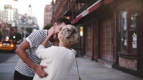 Langzame motie gelukkige Europese meisje het bijten neus die van haar vriend die, van gang langs de straat van de de Stadsavond v stock video
