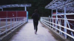 Langzame Motie Geschikte atleet die op kleine brug lopen Achtergrondschot Geschiktheid die in landschap in de voorsteden lopen Ac stock footage