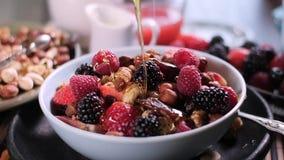 Langzame motie: Gietende honing over bessen en droge vruchten stock videobeelden