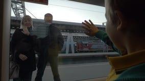 Langzame motie in heilige-Petersburg, Rusland weinig jongen van het treinvenster die aan de grootouders golven die zich op bevind stock video
