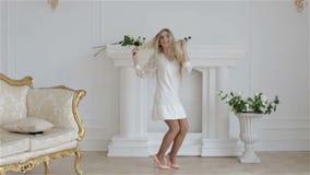 Langzame Motie Het gelukkige mooie meisje in witte modieuze kleding springt in een studio tegen een witte muur stock video