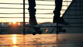 Langzame Motie Het gesilhouetteerde skateboarder met een skateboard rijden en het springen op een zonsondergangachtergrond stock video