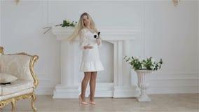 Langzame Motie Het mooie meisje toont haar lang en blondehaar die wervelen dansen Het meisje is in studio tegen een wit stock footage