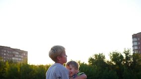 Langzame Motie Het oudere kind werpt zijn lachende broer in de lucht Openlucht activiteiten stock footage