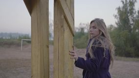 Langzame motie jonge mooie vrouw die langs het de herfststrand lopen en de camera onderzoeken stock videobeelden
