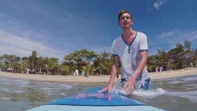 Langzame motie: jonge surfergangen in de oceaan met een surfplank stock videobeelden
