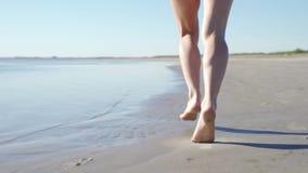 LANGZAME MOTIE: , OMHOOG SLUIT de LAGE HOEK, DOF het Onherkenbare vrouw lopen in de hete de zomerzon langs kust Onbezorgd meisje stock video