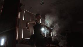 Langzame Motie onherkenbare mooie ballerina die op donker rookstadium presteren Blondevrouw met haar in zwarte ballet stock video