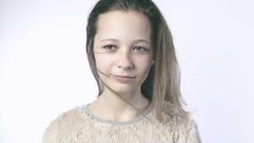 Langzame motie op een tiener De wind blaast het haar van een mooi meisje die zich op een witte achtergrond bevinden Close-up van  stock video