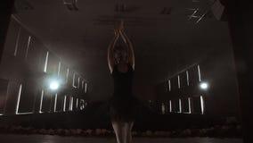 Langzame motie: primaballet op stadium die prestaties in het donkere licht van contra repeteren De lichten van de zaal stock videobeelden