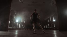 Langzame motie: primaballet op stadium die prestaties in het donkere licht van contra repeteren De lichten van de zaal stock footage