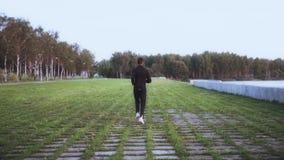 Langzame Motie Sportman die van gezonde levensstijl genieten Achtergrondschot Jonge mens die op grastegels lopen Achter verre men stock video
