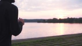 Langzame Motie Sportman die van gezonde levensstijl genieten Jonge vrije mannelijke atleet die bij vreedzaam zonsondergangmeer lo stock video