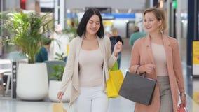 Langzame Motie Twee mooie vrouwen die, bij wandelgalerij lopen en storefronts bekijken winkelen Lachende meisjes binnen bij groot stock video
