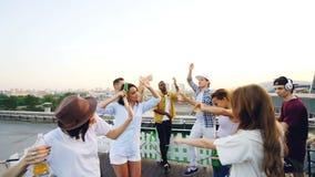 Langzame motie van aantrekkelijke meisjes en van de kerels dansende holding flessen tijdens partij op dak met elektronisch gebrui stock video