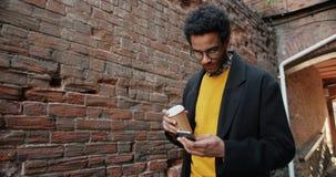 Langzame motie van Afrikaanse Amerikaanse kerel die de koffie van de smartphoneholding in openlucht gebruiken stock video