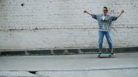 Langzame motie van Aziatische hipster die in openlucht duim-omhoog het tonen met een skateboard rijden stock video