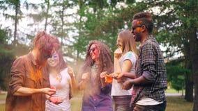 Langzame motie van blije de jeugdmannen en vrouwen die bij partij dansen en poederverf werpen die dan in wolken van helder lachen stock videobeelden