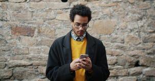Langzame motie van de aantrekkelijke Afrikaanse Amerikaanse mens die smartphone in openlucht gebruiken stock videobeelden