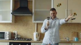 Langzame motie van de aantrekkelijke jonge grappige mens die en met gietlepel dansen zingen terwijl thuis het koken in de keuken stock videobeelden