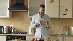 Langzame motie van de aantrekkelijke jonge grappige mens die en met gietlepel dansen zingen terwijl thuis het koken in de keuken stock video
