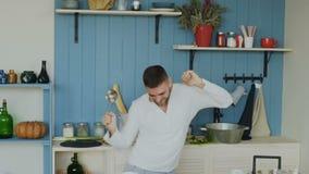 Langzame motie van de knappe jonge grappige mens die en met gietlepel dansen zingen terwijl thuis het koken in de keuken stock footage