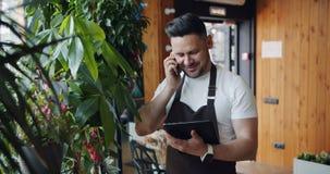 Langzame motie van de manager van de bloemwinkel het spreken op mobiele telefoon en het gebruiken van tablet stock videobeelden