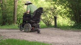 Langzame motie van de mens in een rolstoel die weg met hindernis op de weg afslaan het concept van het gehandicaptenprobleem stock footage
