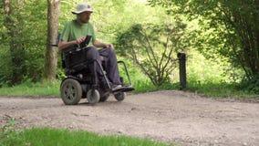 Langzame motie van de mens in een rolstoel die weg met hindernis op de weg afslaat het concept van het gehandicaptenprobleem stock video