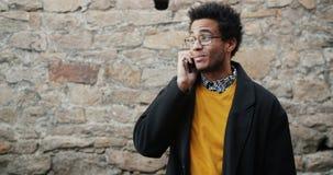 Langzame motie van de vrolijke Afrikaanse Amerikaanse mens die op mobiele telefoon in openlucht spreken stock videobeelden