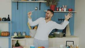 Langzame motie van de vrolijke jonge grappige mens die en met gietlepel dansen zingen terwijl thuis het koken in de keuken stock videobeelden