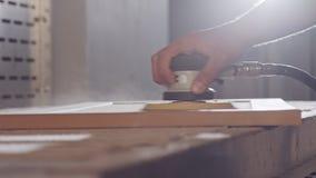Langzame motie van een arbeider die een kabinetsdeur in een meubilairfabriek oppoetsen stock videobeelden