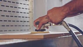 Langzame motie van een arbeider die een kabinetsdeur in een meubilairfabriek oppoetsen stock footage
