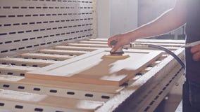 Langzame motie van een arbeider die een kabinetsdeur in een meubilairfabriek oppoetsen stock video