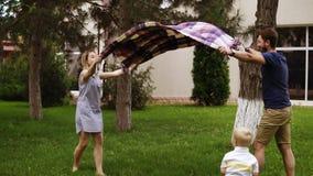 Langzame motie van een jonge familie met een zoon op een groen gazon De ouders spreiden de plaid uit opwinding Blonde weinig jong stock video