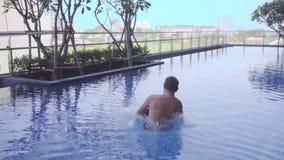 Langzame motie van een mannetje die in de pool springen Close-up die van man benen, en een pool met plonsen tegenkomen springen v stock footage