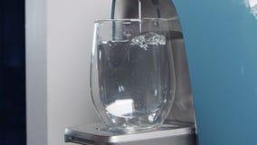Langzame motie van een waterkop die een water filtrerende machine invullen stock video