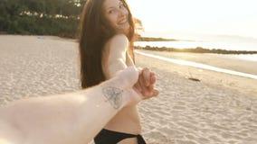 Langzame motie van Follow me schot van jong sexy meisje in een bikini die en mensenhand op het strand in zonsondergang in werking stock video