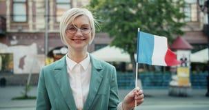 Langzame motie van gelukkig Frans meisje die het nationale vlag glimlachen houden in openlucht zich bevindt stock footage