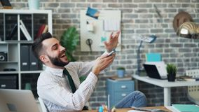 Langzame motie van gelukkige entrepereneur die contant geld werpen die hebbend pret in bureau lachen stock footage